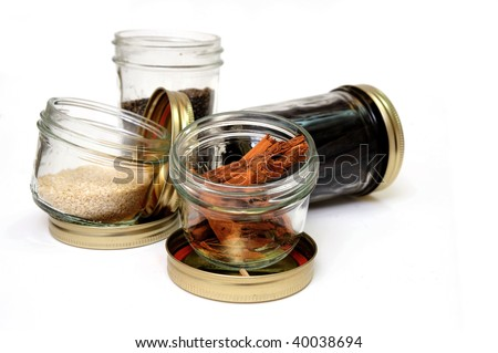 Glass jars of stick cinnamon, vanilla beans, black pepper and sesame seeds on an isolated background