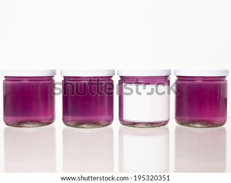 Glass jars with a violet pink liquid against a white background with slight reflection.