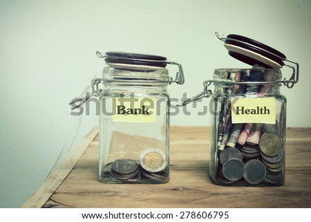 glass jars with coins and 'health' text  - stock photo