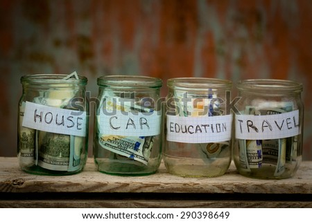 Glass jars with dollars and text: house,car, travel, education - stock photo