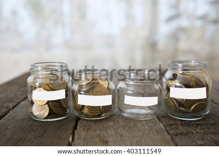 Glass jars with money coins ruble and empty sticker on wooden table - stock photo