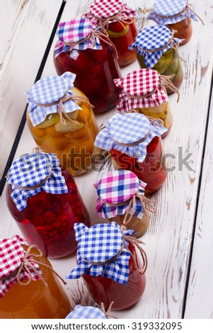 Glass jars with preservation on a background of wooden boards. Canned foods. - stock photo