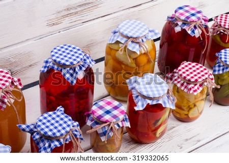 Glass jars with preservation stand on old boards. Harvest of food products. - stock photo