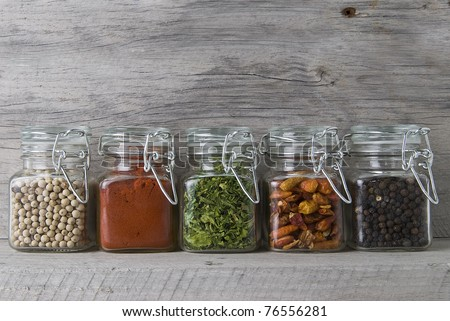 Glass jars with some spices on an old wooden stand. - stock photo