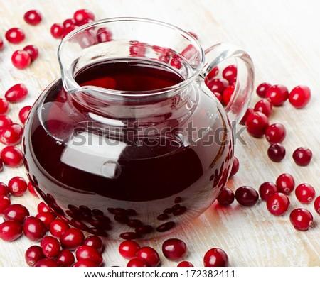 Glass jug of Cranberries juice. Selective focus  - stock photo