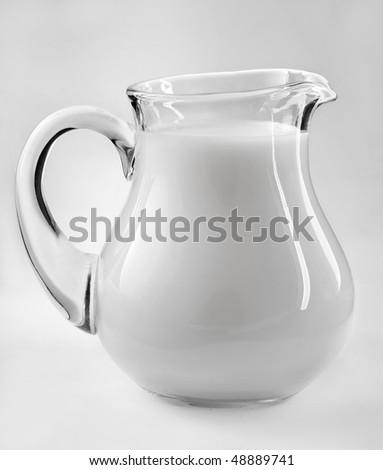 Glass jug of fresh milk isolated on white background - stock photo