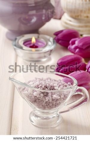 Glass jug of lavender sea salt on white wooden table, tulip flowers in the background - stock photo