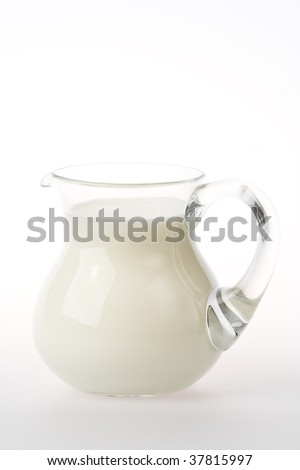 Glass jug with cold milk in it.