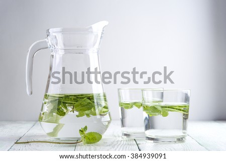Glass jug with cucumber detox water,two glasses on wooden table. Drink for dieting. - stock photo