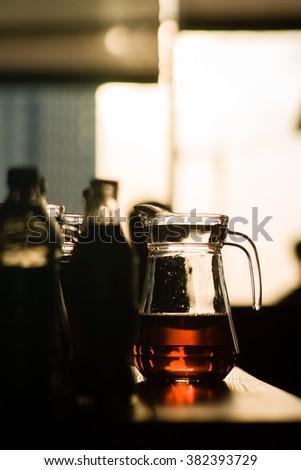 Glass jug with juice backlit - stock photo
