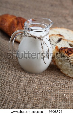 Glass jug with milk and bread on a brown fabric - stock photo