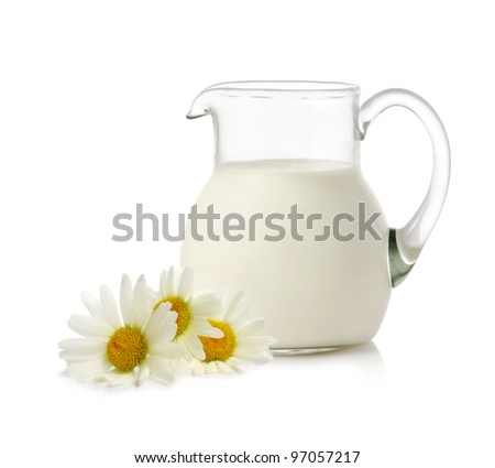 Glass jug with milk and chamomiles on white background - stock photo