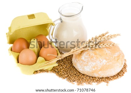 Glass jug with milk, wheat seeds, eggs and roll on white background - stock photo