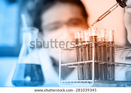 Glass laboratory chemical test tubes with liquid.Man wears protective goggles - stock photo