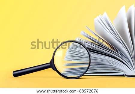 glass magnifying loupe and book on background - stock photo