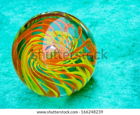 Glass marble ball with colorful swirl isolated on turquoise velvet background. - stock photo