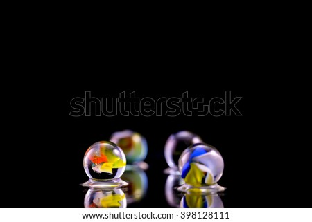 Glass marbles on water with black background