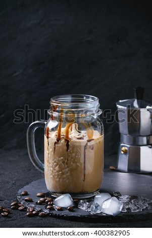Glass mason jar of ice coffee with ice cream and chocolate sauce, served with coffee beans and ice cubes on slate stone board over black textured background. - stock photo