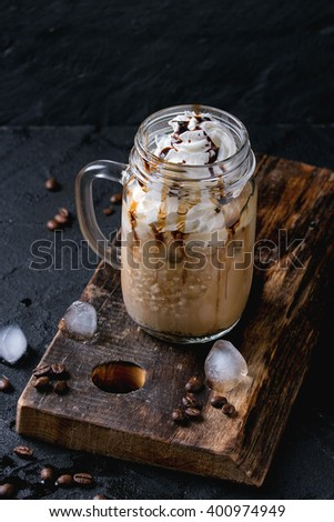 Glass mason jar with ice coffee with whipped cream, ice cream and chocolate sauce, served with coffee beans and ice cubes on wooden chopping board over black textured background. - stock photo