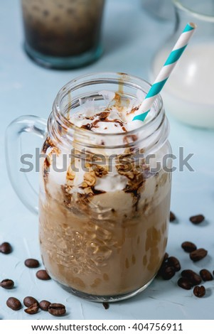 Glass mason jar with ice coffee with whipped cream, ice cream and chocolate sauce, served with coffee beans, coffe pot and jug of milk over light blue textured background. - stock photo