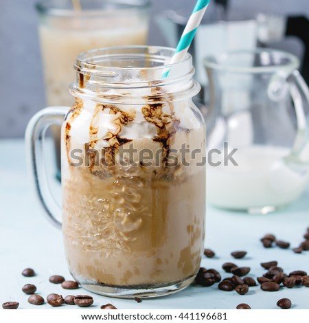 Glass mason jar with ice coffee with whipped cream, ice cream and chocolate sauce, served with coffee beans, coffe pot and jug of milk over light blue textured background. Square image