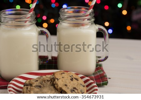Glass mason jars filled with homemade egg nog with cinnamon and red swirled straws and chocolate chip cookies on red and white striped plate and Christmas tree lights in background