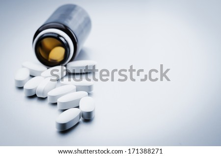glass medical bottle and white pills - stock photo