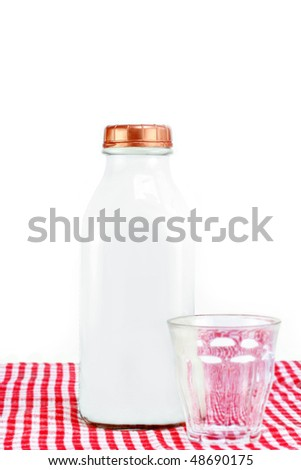 Glass milk bottle with copper top full of milk and an empty glass.  Selective focus on milk bottle.  On white with copy space.