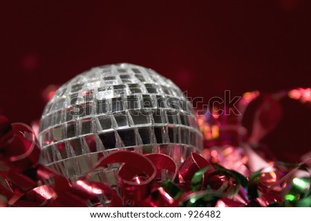 Glass mirror ball Christmas decoration and tree ornament surrounded by red and green ribbon.