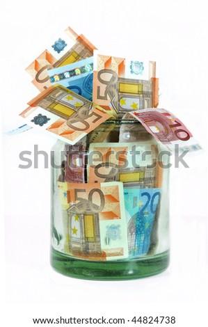 Glass money jar full of Euro banknotes isolated on white - stock photo