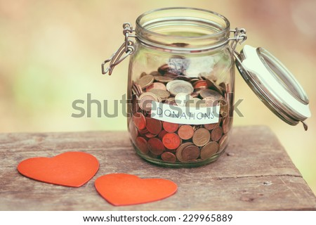 Glass money jar with a label with the word donations on it and two handcrafted wooden heart shapes. - stock photo
