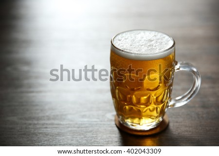 Glass mug of light beer on wooden table