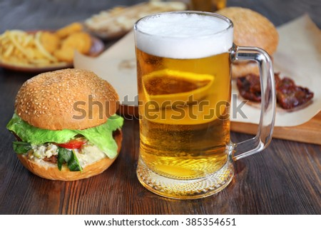 Glass mug of light beer with hamburgers on dark wooden table, close up - stock photo