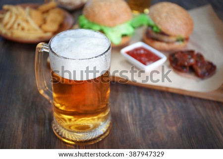 Glass mug of light beer with snacks on dark wooden table, close up - stock photo