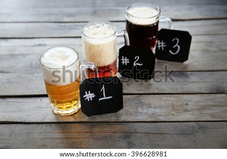 Glass mugs with different sorts of craft beer and numbering on wooden table - stock photo