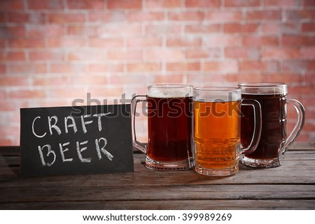 Glass mugs with different sorts of craft beer on brick wall background - stock photo