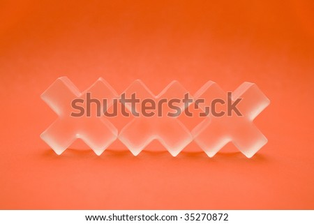 Glass objects spell out XXX. Illustrates sexuality and intimacy. - stock photo