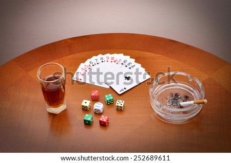 Glass of alcohol, cards, dice and ashtray with cigarette on the brown table - stock photo