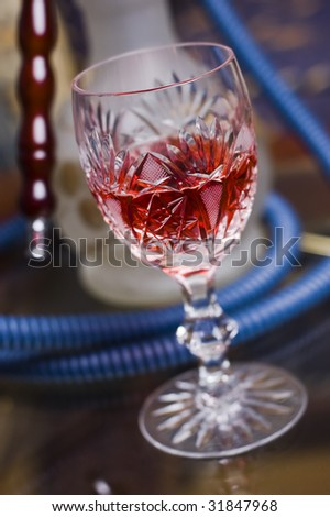 Glass of alcohol in front of hookah - stock photo