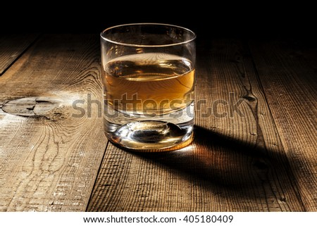 Glass of alcohol on wood table with shadow