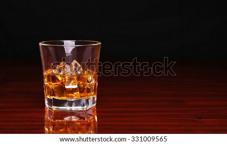 Glass of alcohol scotch whiskey with ice cube on wooden table and black background - stock photo