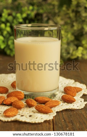 Glass of almond milk with almond on a wooden table - stock photo