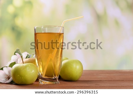 Glass of apple juice and apples on wooden table, on nature background - stock photo