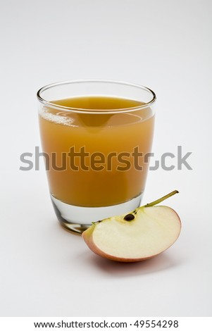 Glass of apple juice isolated on white with apple wedge in foreground - stock photo