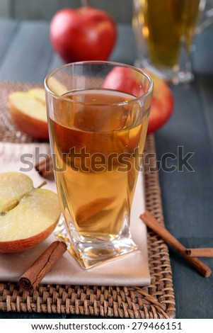 Glass of apple juice on wooden table, closeup