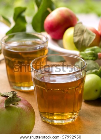 Glass of apple juice with apples in the background. - stock photo
