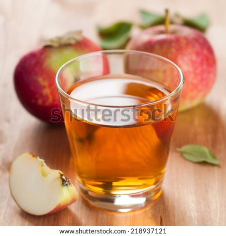 Glass of apple juice with apples on the background, selective focus - stock photo