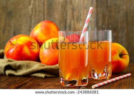 Glass of apple juice with apples on wood background - stock photo