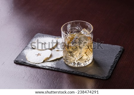 Glass of Apple Liqueur on stone plate on wooden background - stock photo