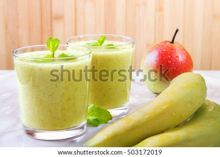Glass of banana and pear smoothie on wooden background